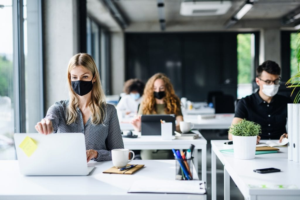 Young people with face masks back at work in office after lockdown.