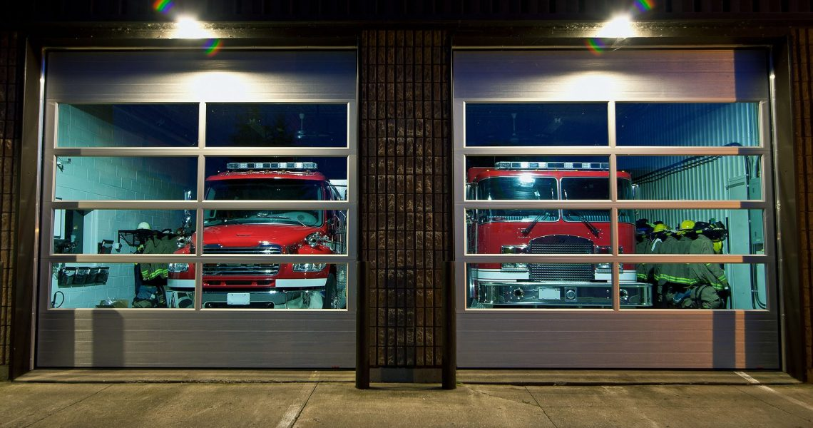 The front of a fire station in the evening with the trucks parked and ready.